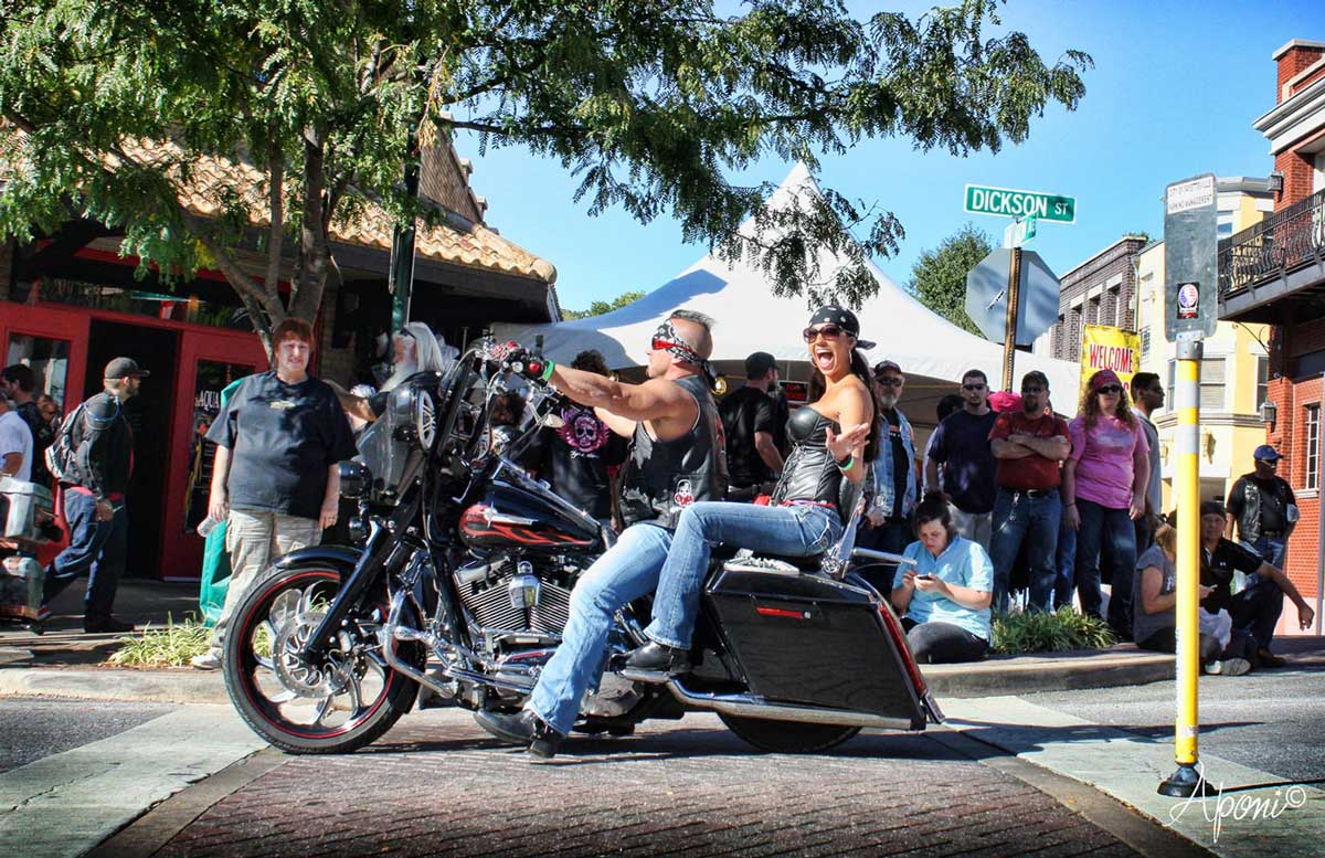 A man and a woman riding on a motorcycle during the Bikes, Blues, and BBQ Rally